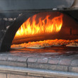 Pizza in old stove, oven - Stock Photo