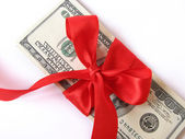 Money with bow of red ribbon — Stock Photo