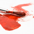 Red paint and old used brush — Stock Photo