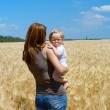 Mother with child at the wheat field — Stock Photo