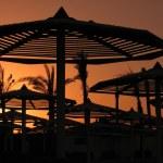 Bloody sunset with beach umbrellas — Stock Photo #1671866