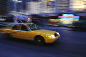 Taxicab speeding down street at night — Foto de Stock