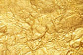 Crumpled gold foil textured background — Stock Photo
