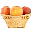 Three tasty peaches in wicker basket — Stock Photo