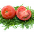 Whole and half of tomato over some dill — Stock Photo #1683213