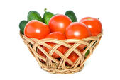 Basket with tomatoes and cucumbers — Stock Photo