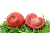 Ripe tomato and half over some dill — Stock Photo