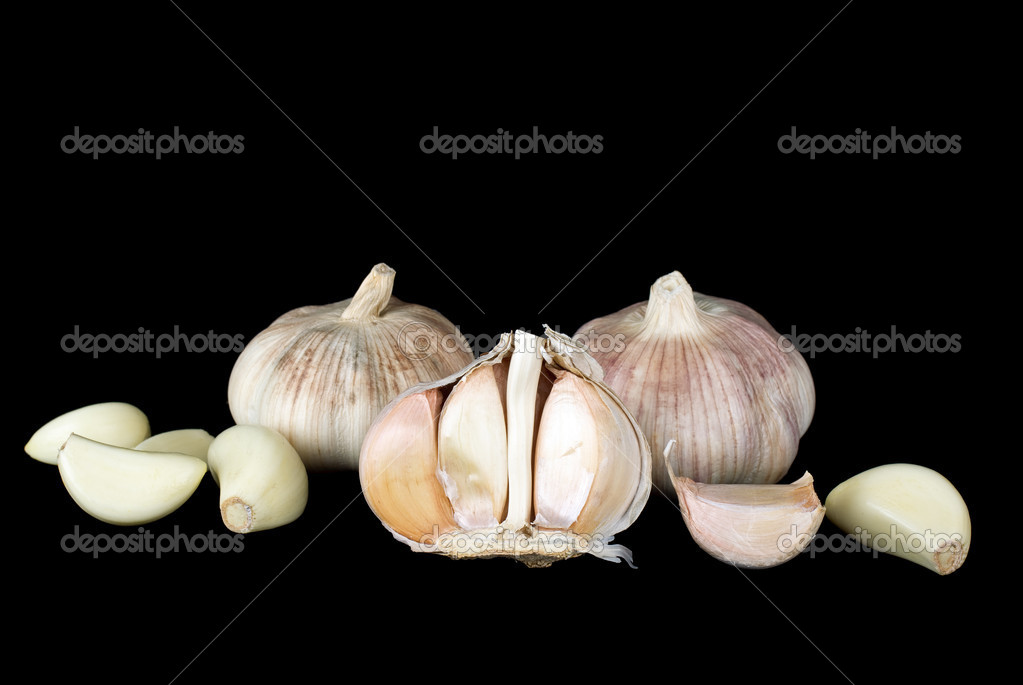 Garlic bulbs and cloves over the black background — Stock Photo #1935374
