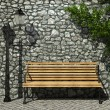 Illuminated stone wall and bench — Stock Photo