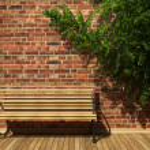 Illuminated brick wall and bench — Stock Photo