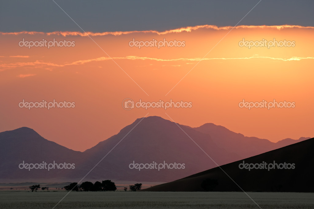 Desert sunrise with silhouettes of sand dunes, mountains and trees, Sossusvlei, Namibia, southern Africa — Stock Photo #1995190