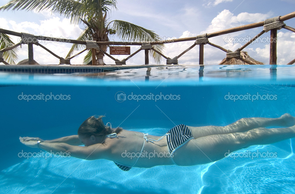 Over and under image of woman swimming in pool — Stock Photo #1644378