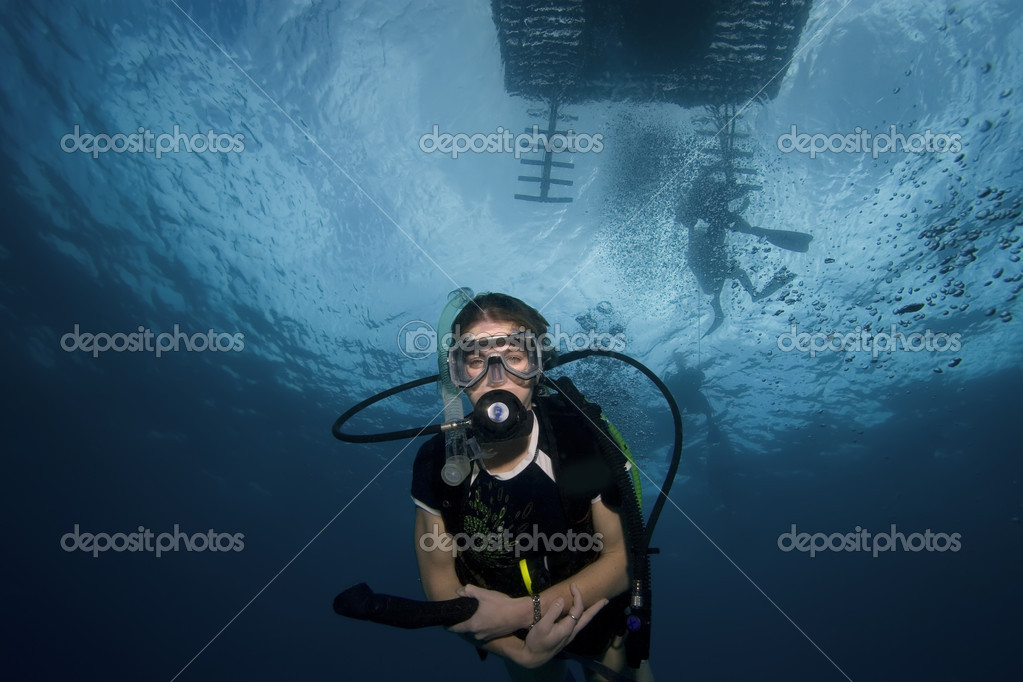Woman scuba diving beneath boat, Key Largo, Florida — Foto Stock #1644434