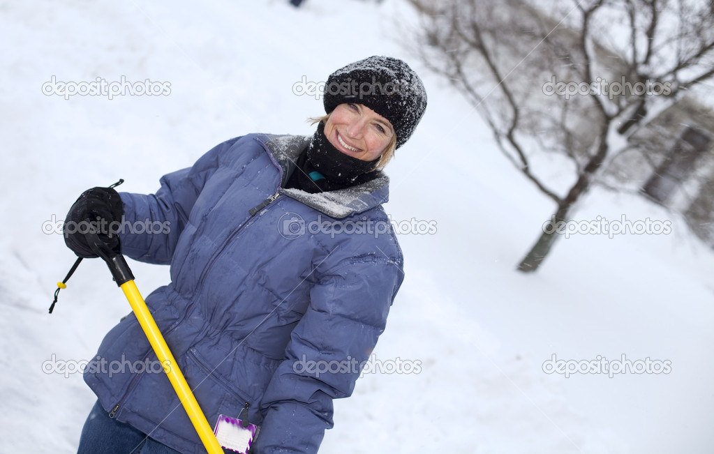 Woman in coat, hat, and mittens shoveling snow after blizzard.  Stock Photo #1644510