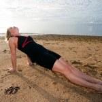 Woman practicing Yoga on tropical beach — Stock Photo