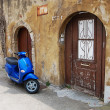 Blue scooter over old wall — Stock Photo