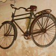 Very old bicycle on wall — Stock Photo