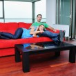 Happy couple relax on red sofa — Stok fotoğraf