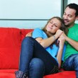 Foto Stock: Happy couple relax on red sofa