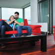 Happy couple relax on red sofa — Stock Photo