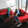 Happy couple relax on red sofa — Stockfoto