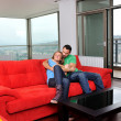 Happy couple relax on red sofa — Stock Photo #1676001