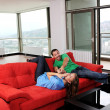 Happy couple relax on red sofa - Stok fotoraf