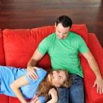 Счастливая пара отдохнуть на красном диване — Стоковое фото