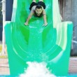 Girl have fun on water slide at outdoor swimmin — Стоковое фото