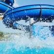 Water slide fun on outdoor pool - Stock Photo