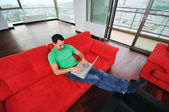 Man relaxing on sofa and work on laptop — Stock Photo