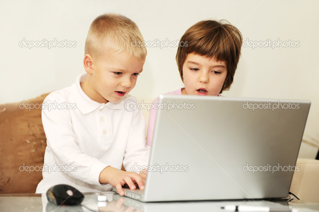 Two happy children playing games and learnig education lessons on laptop computer at home — Stock Photo #1673370