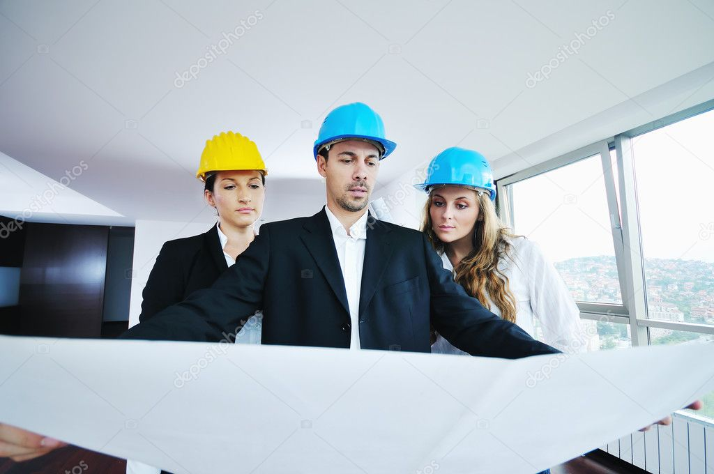 Young arhitect group in big bright modern new apartment looking blueprints and building plans — Stock Photo #1674064