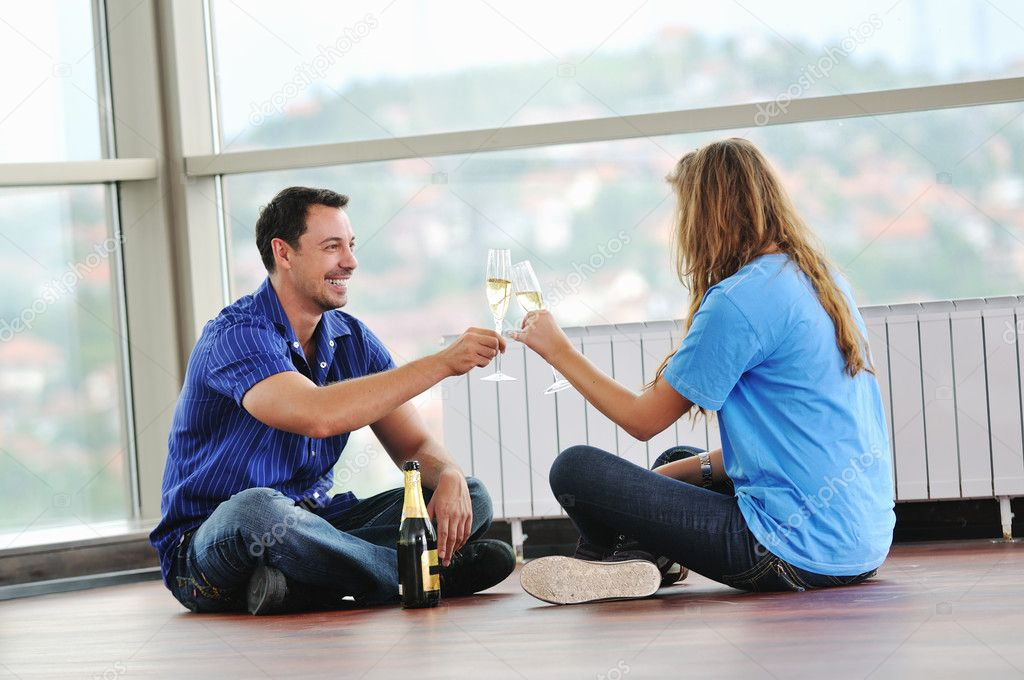Happy couple at big bright comfort apartment celebrate with glasses of champagne — Stock Photo #1674191