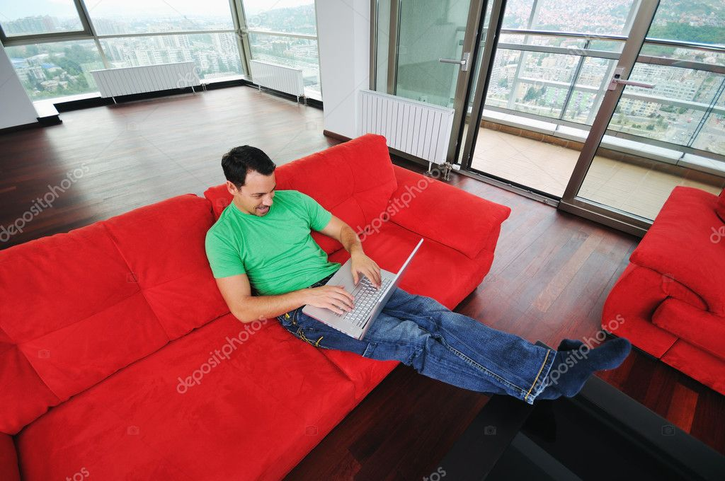 Young man relax on red sofa and work on laptop at home indoor  — Stock Photo #1674259