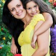 Happy mom and daughter outdoor - Stock Photo