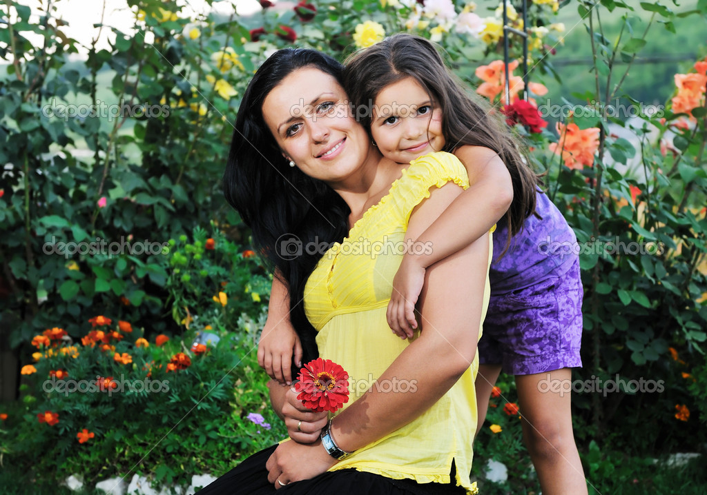 Beautiful mom and daughter outdoor in garden  together with flower have fun and hug  — Stock Photo #1680288