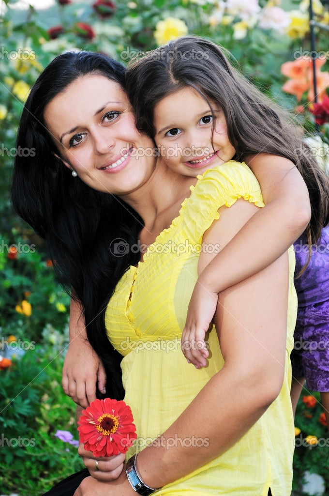 Beautiful mom and daughter outdoor in garden  together with flower have fun and hug   Stock Photo #1680302