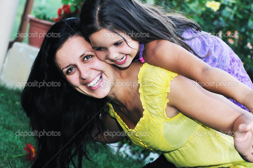 Beautiful mom and daughter outdoor in garden  together with flower have fun and hug  — Stock Photo #1680344
