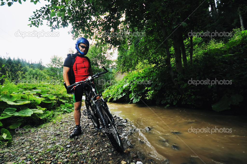 Young man drive mountain bike over water river  Stock Photo #1689534