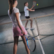 Royalty-Free Stock Photo: Young girls playing tennis game indoor