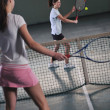 Young girls playing tennis game indoor — Stock Photo