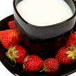 Black cup of milk and strawberries — Stock Photo