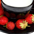 Black cup of milk and strawberries — Stock Photo #1696506