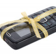 New black mobile phone with gold ribbon — Stock Photo