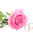 Pink rose and wedding rings — Stock Photo