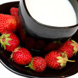 Strawberries and black cup of milk — Stock Photo