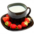 Black cup with milk and strawberries — Stock Photo