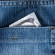 Blue jeans hip-pocket with condom in it — Stock Photo