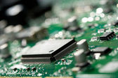Microchip on green circuit board — Stock Photo
